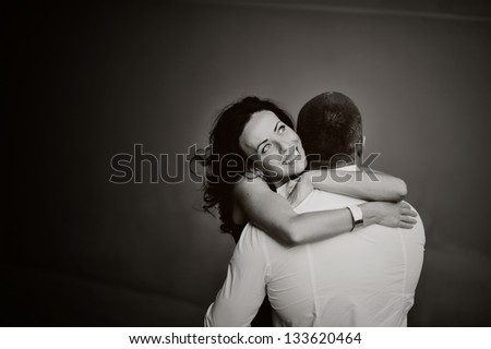 Close-up of a young woman tenderly embracing her boyfriend, black and white