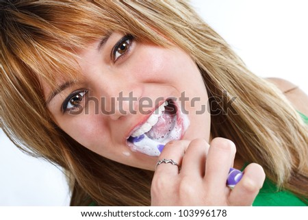 Close-up of a young woman with blond hair, brushing her teeth with foaming toothpaste - isolated on white - stock photo