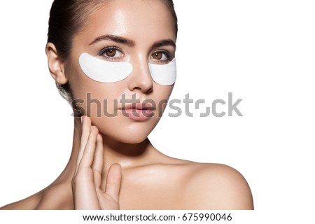 Close-up of a young woman with patches under eyes from wrinkles and dark circles. Isolated on white background #675990046