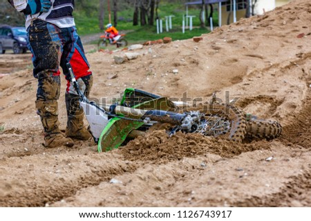 Close-up of accident in mountain bikes race in dirt track in sunshine day time.