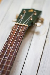 Close up of acoustic ukulele; ukulele strings, saddle, soundhole, ukulele body, neck, fretboard. Fretted folk instrument, wooden, inlay.
