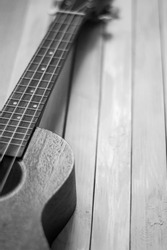 Close up of acoustic ukulele; ukulele strings, saddle, soundhole, ukulele body, neck, fretboard. Fretted folk instrument, wooden, inlay.