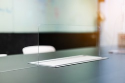 Close up of acrylic plexiglass separator standing partition wall with pass-through on the desk in the meeting room. Social distancing in offices during the Covid-19 pandemic. Precaution and safe.