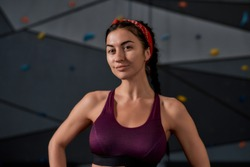 Close up of active young woman in sportswear looking at camera, standing against artificial training climbing wall. Concept of sport life and rock climbing. Horizontal shot. Focus on person
