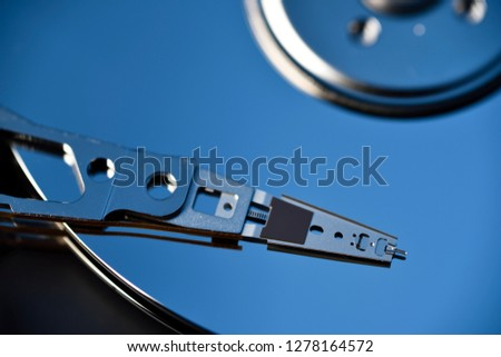 Close up of actuator arm on platter of hard disk drive data storage for laptop