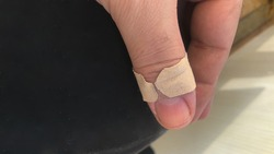 close up of adhesive bandage on thumb of a male person