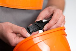 close-up of adjusting size of construction helmet for head, an element of construction workwear, man hand chooses number on strap