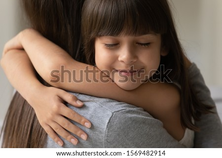 Close up of adorable brown-haired cutie little daughter face with closed eyes cuddle her mother showing sincere love and strong attachment heartfelt moment, new mom for adopted grateful child concept