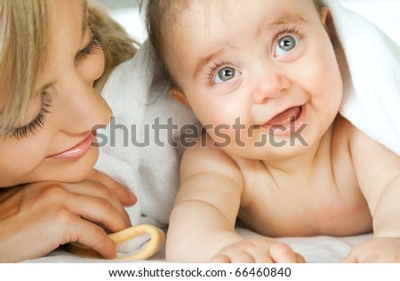 Close-up of adorable little baby face smiling lying next to her mother