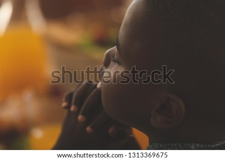 Close-up of African American boy with hand clasped and eyes closed praying at dining table at home
