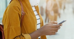 Close up of African American female hand holding smartphone device and tapping on screen. Outdoor. Woman tourist scrolling and typing on mobile phone at street on bus stop.
