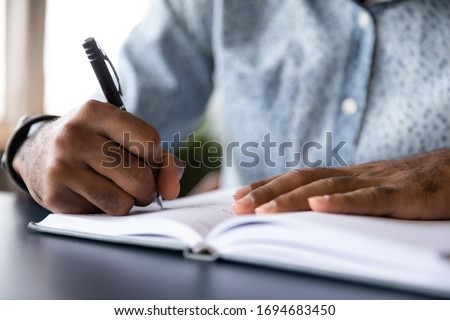 Close up of african American male student busy handwriting in notebook preparing for exam or test, biracial man worker make notes or list writing down, planning or thinking at workplace in office
