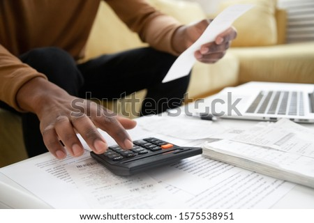 Close up of african American man calculating using machine managing household finances at home, focused biracial male make calculations on calculator paying bills, account taxes or expenses