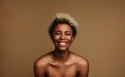 Close up of african american woman laughing. Woman with short curly hair on brown background.