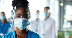 Close up of African American woman physician in face shield looking to camera in clinic. Portrait of female doctor or nurse in medical mask and goggles in hospital. Docs talking on background Covid-19