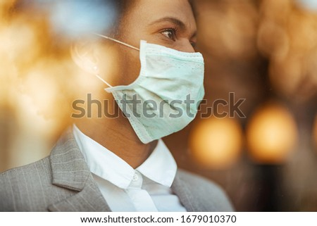 Close-up of African American woman wearing protective face mask. The view is through the glass.