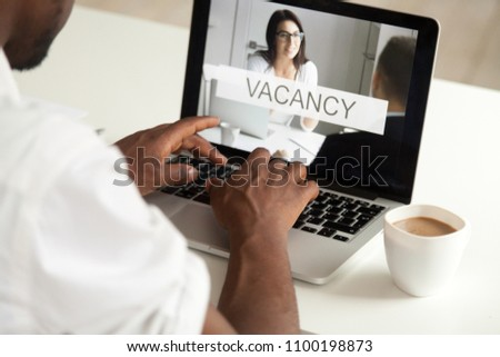 Close up of African American worker replying to vacancy offer online, looking for job using website pages, cv applications, browsing resume, open positions surfing net. Employment, recruiting concept #1100198873