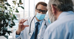 Close up of African American young handsome male doctor specialist in medical mask talking with Caucasian old patient explaining new coronavirus vaccine on medical consultation, vaccination concept