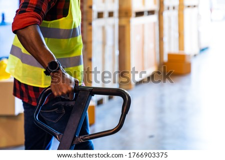 Close up of african black warehouse worker hand hold hand pallet jack in distribution warehouse with copyspace. Business warehouse and logistic concept.