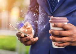 Close up of african businessman holding coffee to go and using brand new mobile phone with functional icons