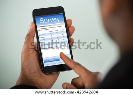Close-up Of African Businesswoman Filling Online Survey On Mobile Phone #423942604