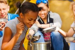 Close-up of African girl cooking soup at campsite