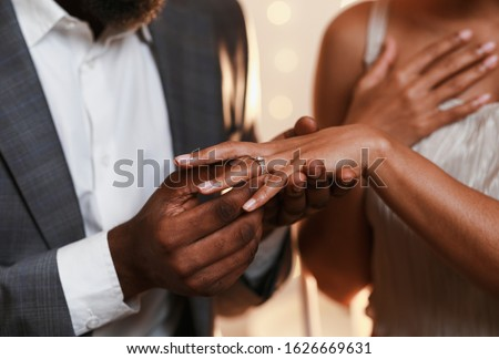 Close up of african man in love putting wedding ring on his woman finger Stock photo ©