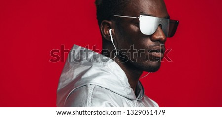 Close up of african man wearing silver outfit and mirrored stylish sunglasses with earphone. Young guy styled in futuristic outfit in studio.