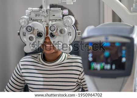 Close-up Of african teen girl Doing Eye Test On Phoropter, African teen girl checking on her eye with optometry machine.