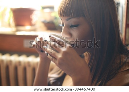 Close up of African woman drinking coffee.