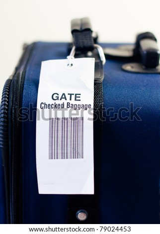 Close up of airline checked baggage label on blue suitcase. Vertical view. Selective focus. - stock photo