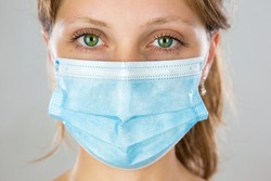 Close-up of alert young blonde woman with face mask looking into camera. Attentive girl with protection over mouth and nose from front view in vertical composition.