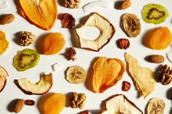 Close up of almonds, dried apricot, raisins, walnuts, dried apples and kiwi on white background. Concept of organic healthy assorted dried fruit for snacks.
