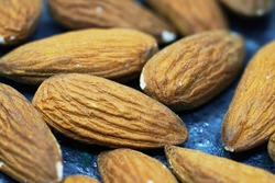Close up of almonds. The nuts lie on a ceramic dark plate. Focus on one of the almonds. They deliver a massive amount of nutrients. They also contain a decent amount of copper, vitamin B2.