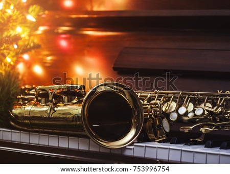 close up of alto saxophone  on the Piano Keys with Christmas tree and decoration light, in the night of Christmas season, Christmas background