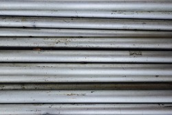 Close up of aluminum pipe poles laying on the ground. Pipes look like horizontal silver tubes. All pipes have character with scrape marks and pitting.