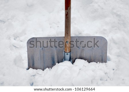 Close up of aluminum snow shovel in deep snow