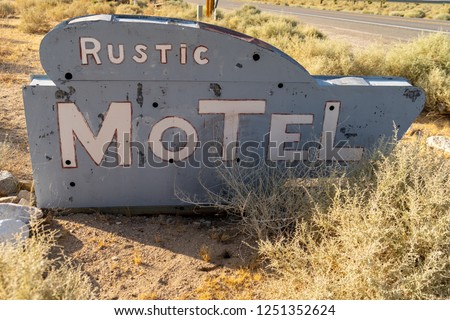 Close up of an abandoned generic rustic retro motel sign is falling apart and decaying in the California deser