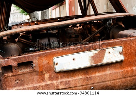close up of an abandoned rusty car with a empty license plate after a fire