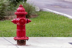Close up of an above ground red pressurized wet-barrel fire hydrant and not a dry-barrel type plug found in Fort Lauderdale Florida, United States and Broward County.