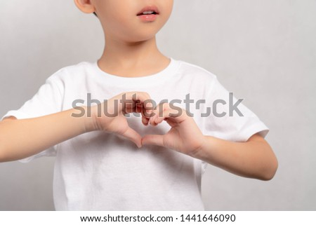 Close up of an adorable little boy doing hand sign heart shape, showing Love, Hope, Care, Compassion. Health care, Family insurance, Charity, Organ donate concept, World health, World heart day.