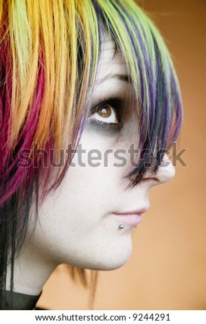 Close-up of an alternative girl with multi-colored hair looking up