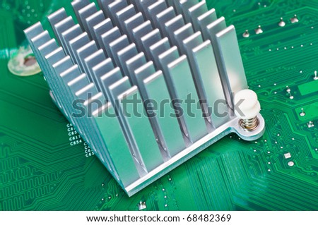 Close-up of an aluminum heatsink mounted on a green computer circuit board