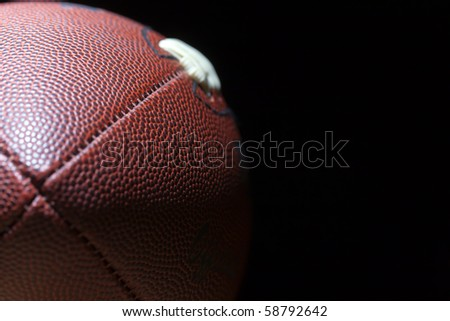 close up of an american football against a black background