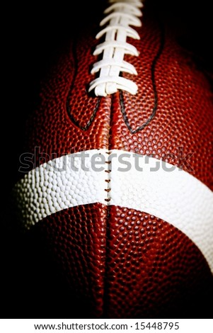 close up of an american football against a black background vertical