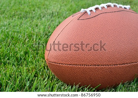 Close-up of an American Football on Real Grass Turf of a Football Field