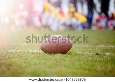Close up of an american football on the field, players in the background #1049356976