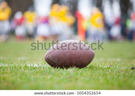 Close up of an american football on the field, players in the background #1054352654