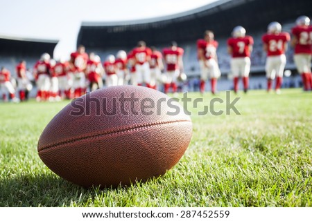 Close up of an american football on the field, players in the background #287452559