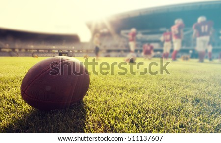 Close up of an american football on the field, players in the background #511137607